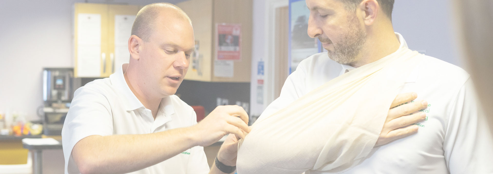 2 male first aid trainers demonstrating application of sling